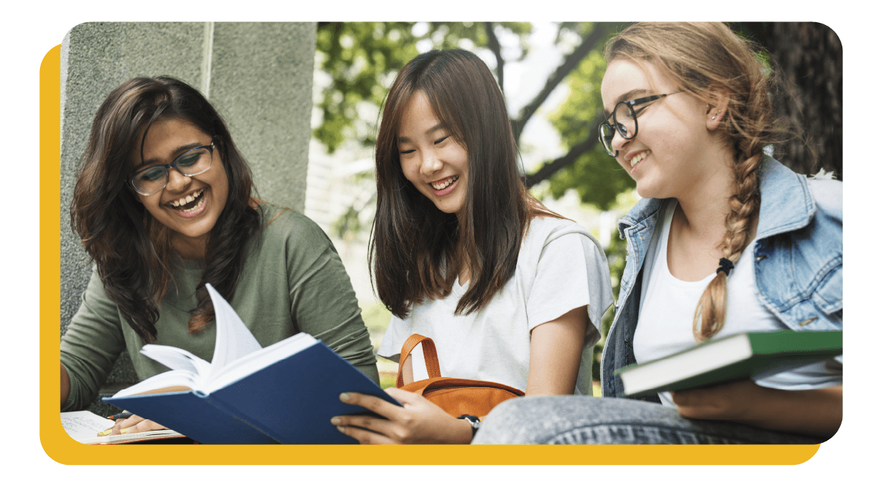 Three happy students looking at a book